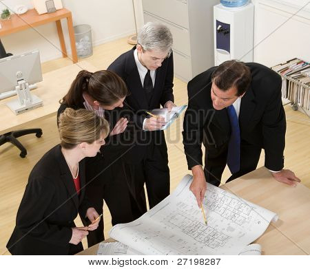Architect co-workers reviewing blueprints