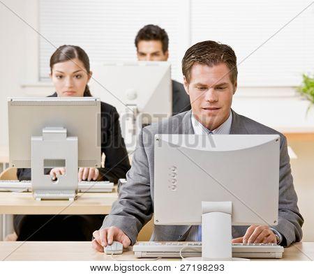 Geschäftsmann arbeiten auf Computer mit co-Arbeitnehmer im Hintergrund