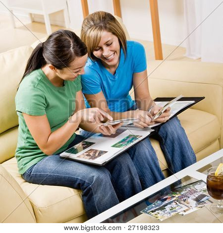 Amigos sentados en el sofá en la sala de estar mirando el álbum de fotos y recordar momentos felices