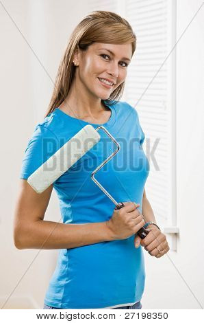 Self-sufficient woman holding paint roller and renovating home