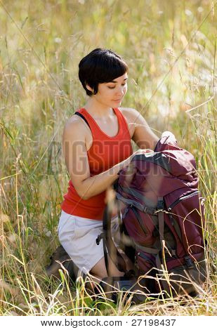 Woman opening backpack in field