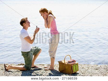 Novio proponiendo a novia cerca de arroyo