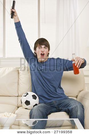 A young man is sitting on the couch in his living room and watching a sports game.  He is holding a remote control, a soda, and there is a soccer ball right next to him. Vertically framed shot.