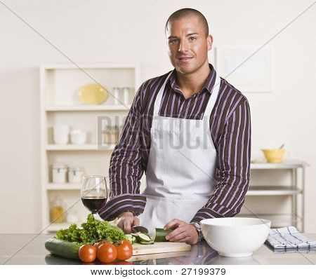 A young man is in his kitchen and is chopping vegetables to prepare a meal.  He has a glass of wine and is looking at the camera.  Horizontally framed shot.
