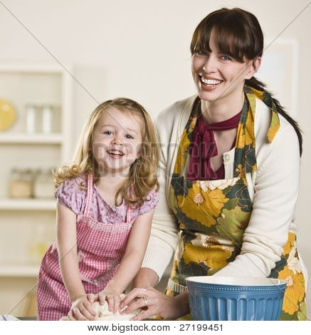 Brunette mom and blond daughter making bread on the kitchen counter, while wearing aprons. Both are kneading dough and looking at the camera. Square