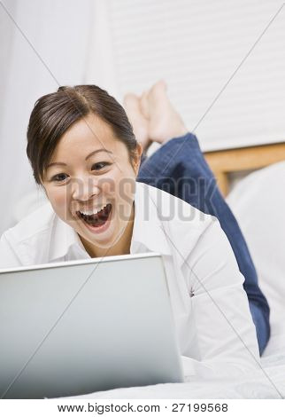 A cute young asian woman smiling excitedly at her laptop screen.  She is relaxing in bed. Vertically framed shot.