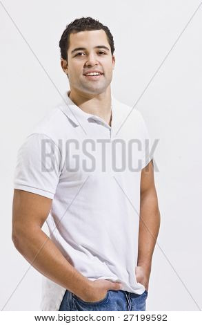 An attractive man posing in blue jeans and a polo shirt. He is smiling directly at the camera. Vertically framed shot.