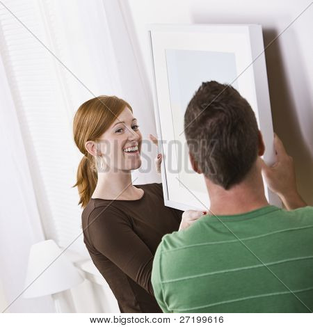 An attractive young couple hanging a picture frame in their home. Square composition.