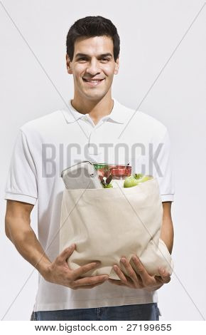 Hombre hispano atractivo sosteniendo una bolsa de comestibles y sonriendo a la cámara. Tiro vertical enmarcado
