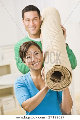 A happy and attractive young couple carrying a roll of carpet together.  They are smiling at the camera.  Vertically framed shot.