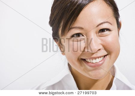 The headshot of a beautiful asian woman smiling.  She is isolated with a white background and is smiling at the camera.  Horizontally framed shot.
