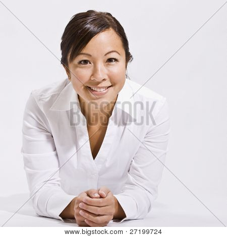 A young woman wearing white is in an isolated white room and is smiling at the camera.  Square framed shot.
