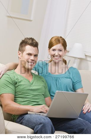 A young, attractive couple is seated together on a couch and are working on a computer.  They are smiling at the camera.  Vertically framed shot.