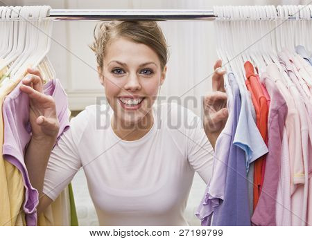 A young, attractive woman is standing in a closet and looking through clothes.  She is smiling at the camera.  Horizontally framed shot.