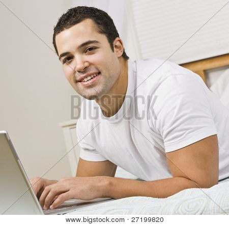 A man relaxing on a bed and using a laptop computer.  He has his fingers on the keyboard and is smiling at the camera. Square framed shot.