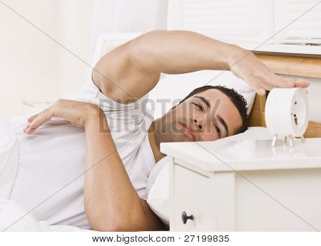 A man lying in bed.  He is reaching his arm to touch an alarm clock.  He looks tired. Horizontally framed shot.