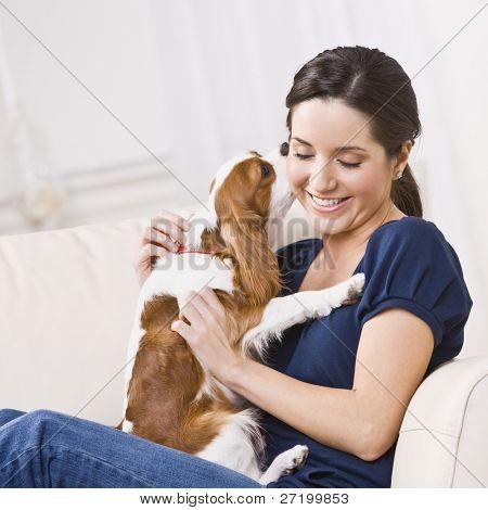 eine attraktive junge Frau sitzt auf einer Couch und wird von einem Hund, den sie hält küßte. Sie ist