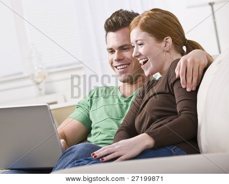 A young and attractive couple sitting together and viewing a laptop screen. They are smiling and laughing. Horizontally framed photo.