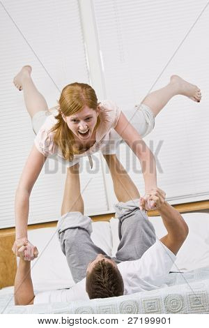 A couple playing on a bed.  The male is balancing the female in the air with his feet. She is laughing.  Vertically framed photo.