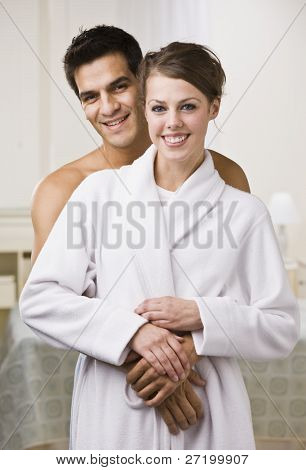 An attractive young couple looking relaxed and happy. The female is wearing a bathrobe and they are smiling directly at the camera. Vertically framed photo.
