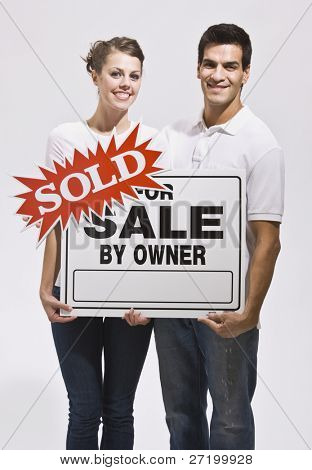 A young couple holding a real estate sign that reads 'sold.' They are smiling and are facing the camera. Vertically framed photo.