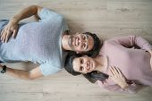 Smiling couple lying on hardwood flooring looking at camera                               poster