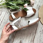 White Female`s Sandals On A Wooden Background poster