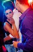image of cheating  - Attractive woman flirting with man in nightclub - JPG