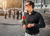 Young Man In Black Shirt Stand Outside And Hold Red Rose In Hands. He Looks Aside Through Sunglasses poster