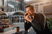 Cheerful Young Man Sit At Table Outside And Eat Salty Roll. He Keep Eyes Closed. Guy Talk On Phone.  poster