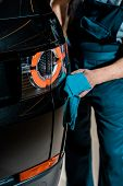 Partial View Of Auto Mechanic Cleaning Black Car With Rag At Mechanic Shop poster