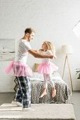 Happy Father And Cute Little Daughter In Pink Tutu Skirts Dancing At Home poster