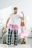 Father And Adorable Little Daughter In Pink Tutu Skirts Having Fun At Home poster