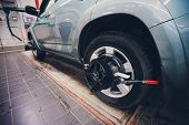 Mechanic Tuning Aligner For Wheel Alignment In Garage Closeup. Professional Car Maintenance In Moder poster