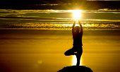 Постер, плакат: Девушка делает йога в закате на вершине горы
