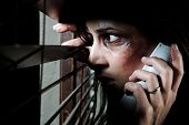 foto of domestic violence  - Fearful battered woman peeking through the blinds to see if her husband is home while calling for help - JPG