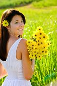 stock photo of summer fun  - Adorable girl with flowers poses in a field during summer afternoon - JPG