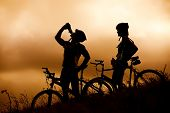 Attractive, healthy couple drink from their water bottles on mountain bikes, silhouette at sunset. a