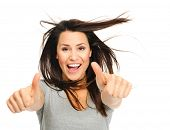 image of windswept  - Pretty woman is jubilant with windswept hair  and thumbs up - JPG