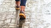 Walk On Wet Melted Ice Pavement. Back View On The Feet Of A Man Walking Along The Icy Pavement. Pair poster