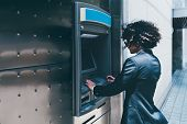 Side View Of A Businessman Withdrawing Money From His Bank Card Using An Outdoor Atm;  A Curly Man E poster