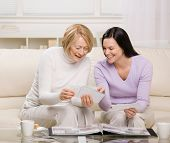 Adult mother and daughter enjoying photo album in livingroom