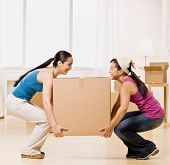 Happy women moving into new home and carrying large, heavy cardboard box