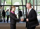 Businesspeople meeting and shaking hands in office lobby