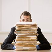 Overworked, frustrated businessman looking at pile of file folders