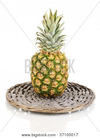 Pineapple on wicker mat isolated on white