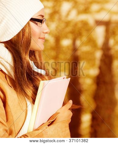 Picture of attractive student female in autumnal university garden, closeup side view portrait of pretty teen girl holding textbook and enjoying warm autumn weather on school backyard