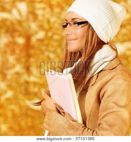 Image of happy cheerful student girl with textbooks, closeup portrait of smart female wearing warm hat and stylish glasses, cute teen female stand on autumn background, education concept