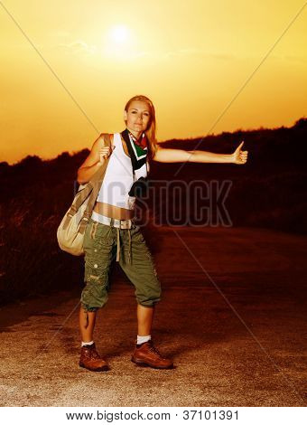 Image of active sporty girl traveling hitchhike, blond woman on road waiting for car, tourist female standing on highway with raised hand and stop auto, conceptual of vacation, adventure