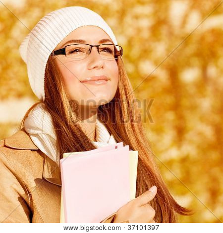 Picture of romantic student girl with textbook on yellow foliage background, closeup portrait of smart female wearing warm hat and stylish glasses, back to school, education concept